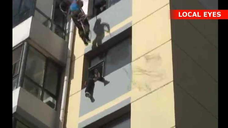 En modig brandmand firer sig ned med et reb fra taget