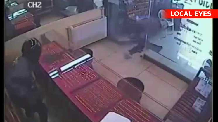 En af røverne stormer ud da ejeren skyder efter dem