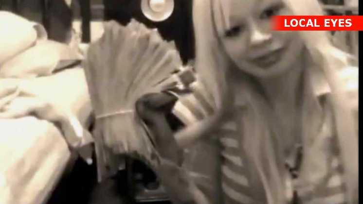 Hun viser udbyttet fra et bankrøveri frem